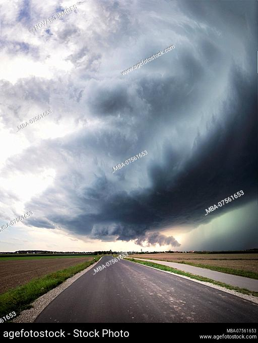 Panorama of a super cell with a low-lying wall cloud, a healthy upwind base and a glowing green precipitation core over a country road near Heilsbronn, Bavaria