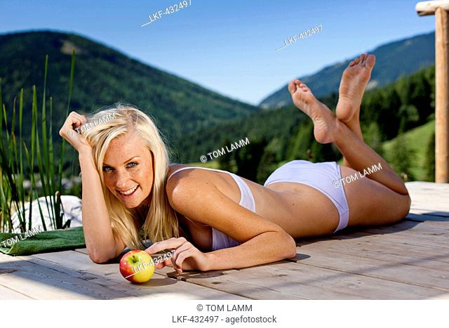 Young woman with an apple lying on a jetty, Fladnitz an der Teichalm, Styria, Austria
