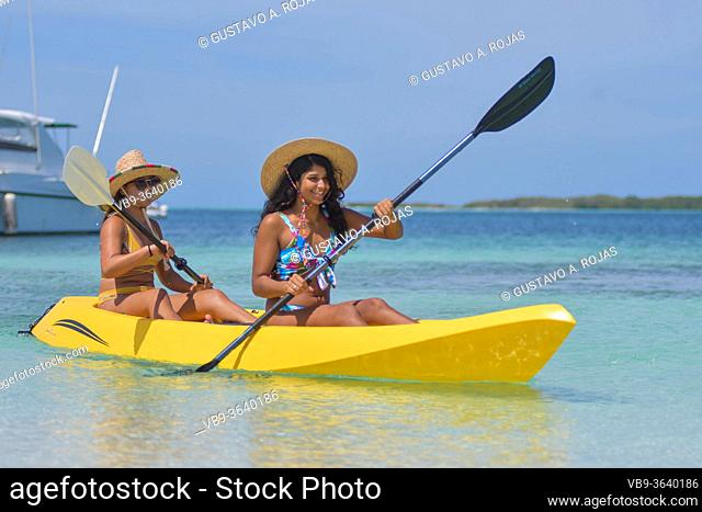 Two young Hispanic women paddling in yellow kayak at summer travel destination. Exotic Caribbean beach with turquoise water sea