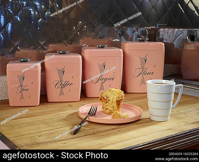 Coffee and muffin on countertop in front of vintage, kitchen canisters