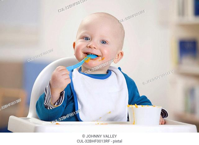 Smiling baby boy eating in high chair