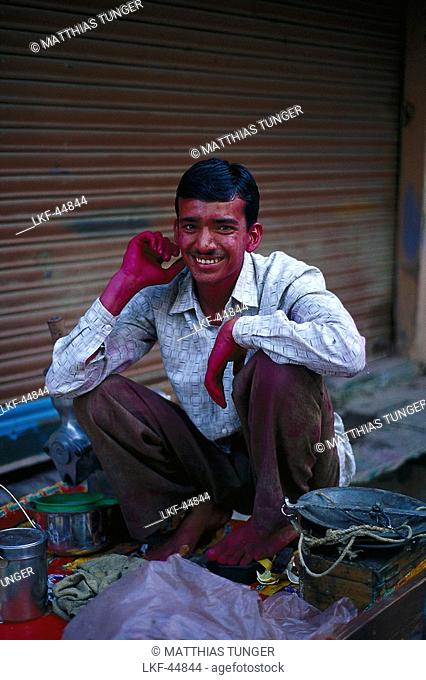 Painter, man with purple hands cowering amidst paint pots and equipment, Khajur, India