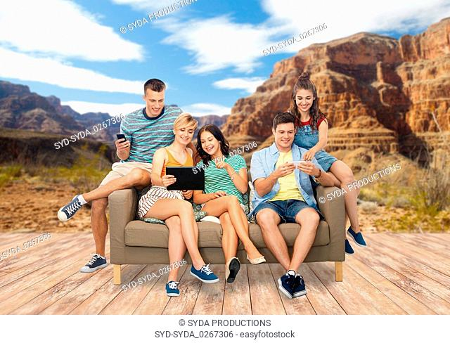 friends with modern gadgets over grand canyon