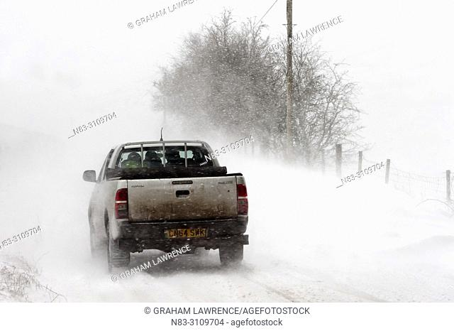 A vehicle drives along the B4520 (Brecon Road) through a blizzard on the Mynydd Epynt moorland, near Builth Wells in Powys, Wales, UK