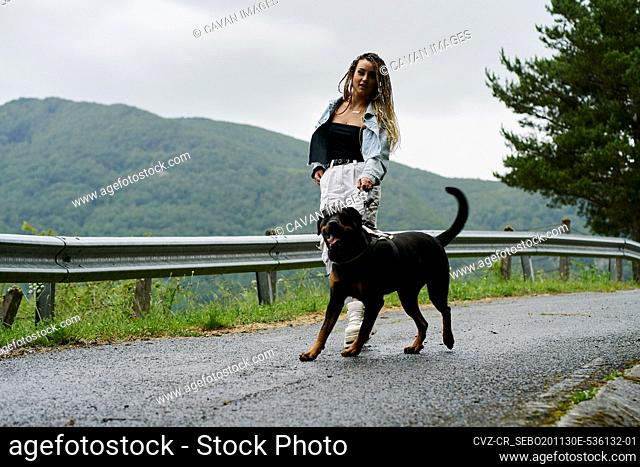Young woman with blonde braided hair wearing a denim jacket and white jean walking her dog on a rainy day