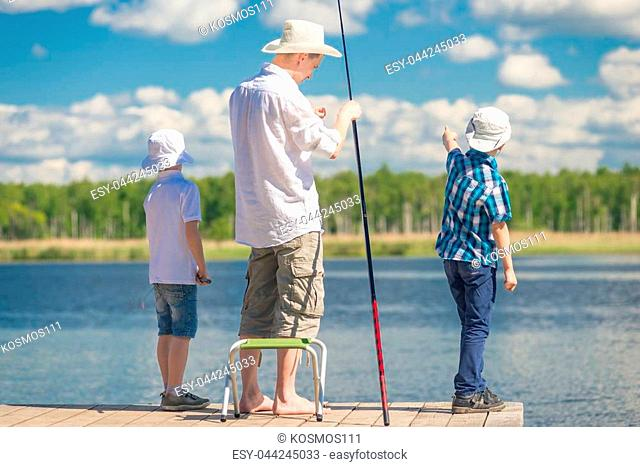 boys with father on fishing in a beautiful place on the lake