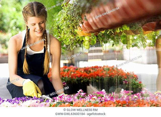 Woman working in a greenhouse and smiling
