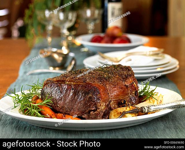 Herbed Roast Beef on a Platter with Fresh Rosemary and Vegetables