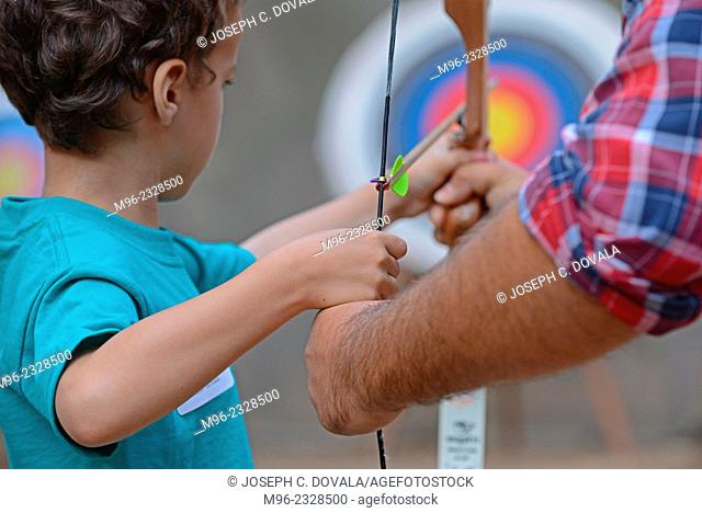 Boy pulling bow string back with help from adult, Malibu, California, USA