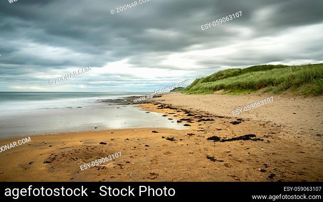 Dramatic sky over a beach, seen at Cocklawburn Beach near Berwick-upon-Tweed in Northumberland, England, UK