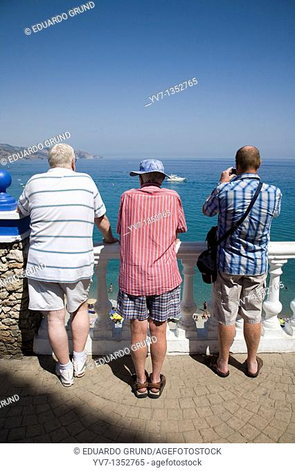 Three retirees looking at a landscape from a balcony, Nerja, Andalucia, España