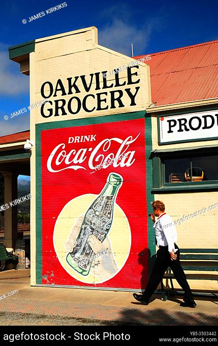 An adult man walks past a billboard at the classic Oakville Grocery in Californiaâ. . s Napa Valley