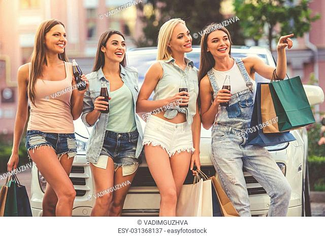 Beautiful stylish girls are holding shopping bags, drinking beverages, talking and smiling while standing near their car outdoors