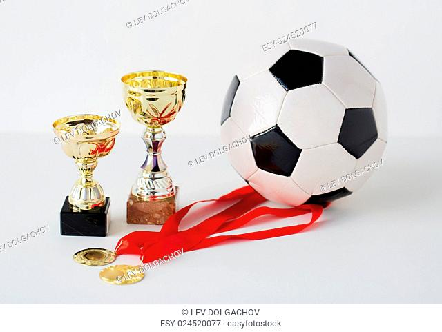 sport, achievement, championship, competition and success concept - close up of football or soccer ball with golden medals and cups over white background