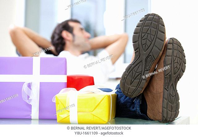 A man rests happily next to a pile of presents