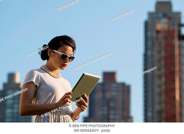 Mid adult women using digital tablet, Manhattan, New York