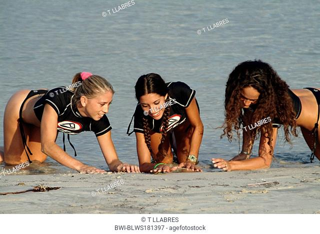 three attractive young woman in swimwear at sandy beach, Spain, Balearen, Majorca