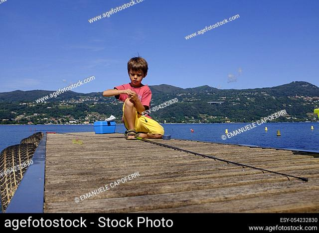 Child on the dock preparing fishing pole, Lake Maggiore, Ranchi, Lombardy, Italy
