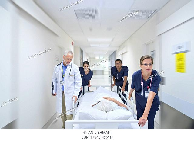 Emergency Medical Team Wheeling Patient Along Hospital Corridor