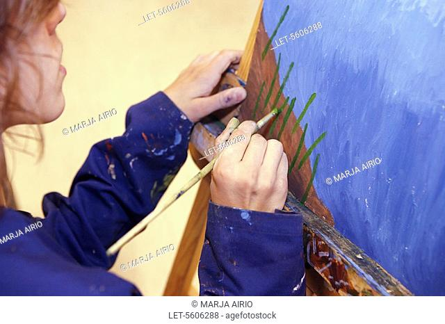 Pupil paints with oil colours in visual arts class