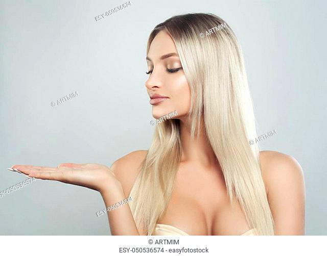 Cute Blonde Woman Spa Model with Healthy Skin, Long Hair and Natural Make up Showing Empty Copy Space on the Open Hand. Product Placement and Advertising...