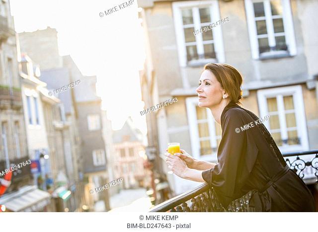 Caucasian woman drinking orange juice on balcony in city