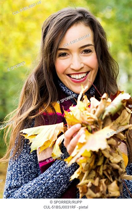 Smiling woman holding autumn leaves
