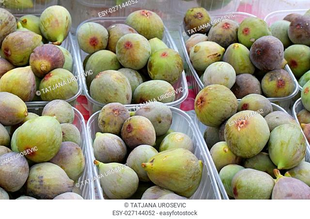 Fresh organic figs piles in plastic containers