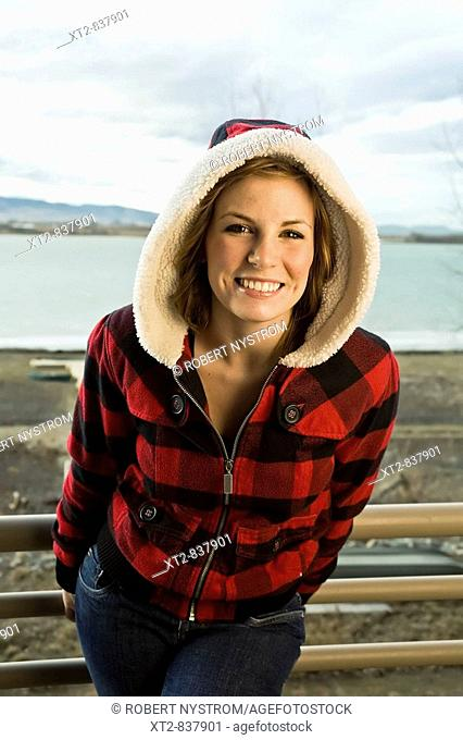 A beautiful young woman standing on a deck in front of a frozen lake in Colorado (USA) smiling