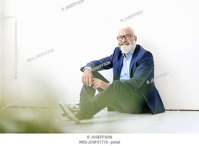 Smiling mature man sitting on the floor