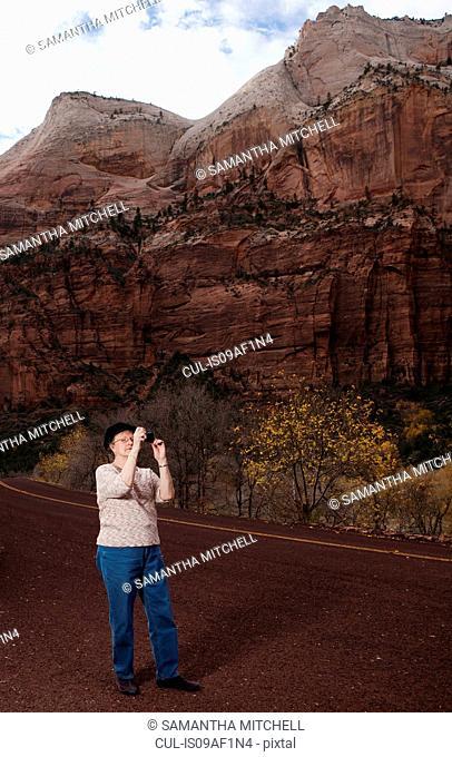 Senior woman taking photograph in Zion National Park, Utah, USA