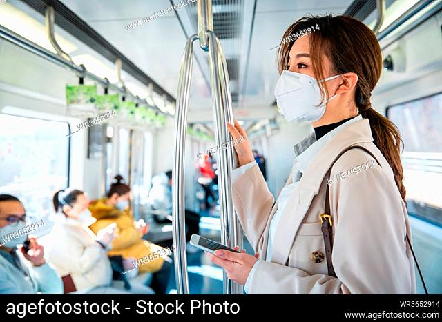 Wearing a mask of the young women take the subway