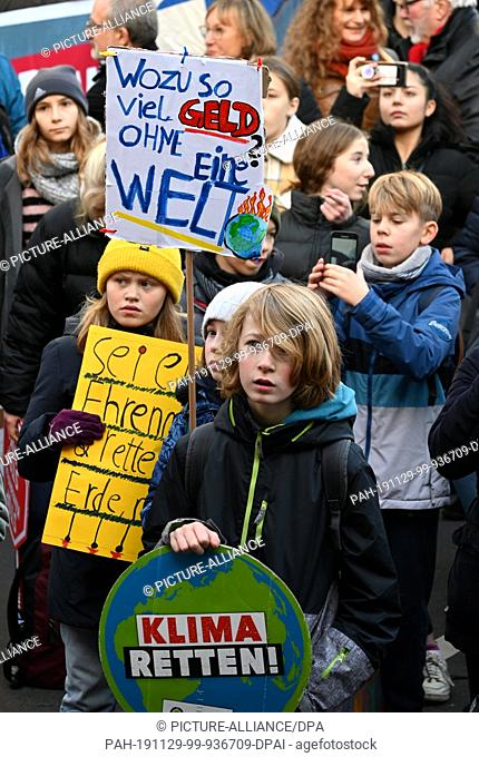 "29 November 2019, North Rhine-Westphalia, Cologne: Children hold a demonstration for climate protection with signs saying """"Why so much money without a world?""""..."