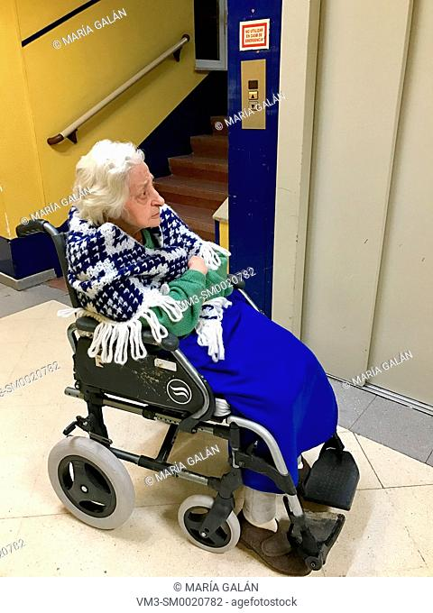 Old lady sitting in a wheelchair, waiting for the elevator