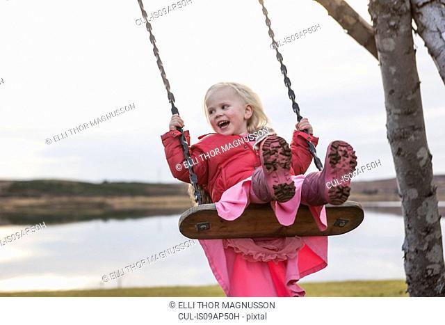 Female toddler swinging on playground swing, Reykjavik, Iceland