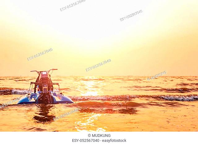 The jet ski is over the water sea between sunset
