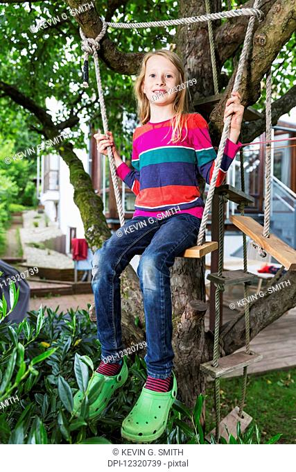 Portrait of a young girl sitting on a tree swing in her backyard; Darmstadt, Hessen, Germany