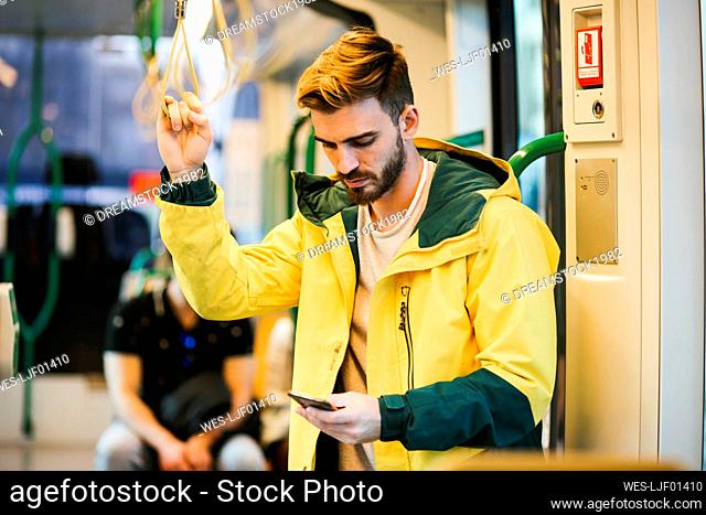 Man using cell phone in subway