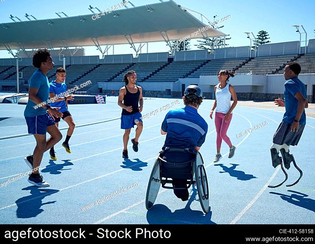Diverse athletes warming up on sunny blue sports track