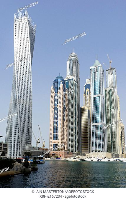 Very tall high-rise apartment towers and Cayan Tower on left in Marina district in new Dubai in United Arab Emirates
