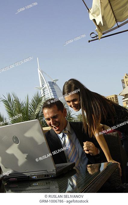 Businesspeople working on laptop in Dubai (Burj Al Arab hotel in background)