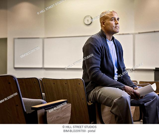 Male professor sitting in empty lecture hall