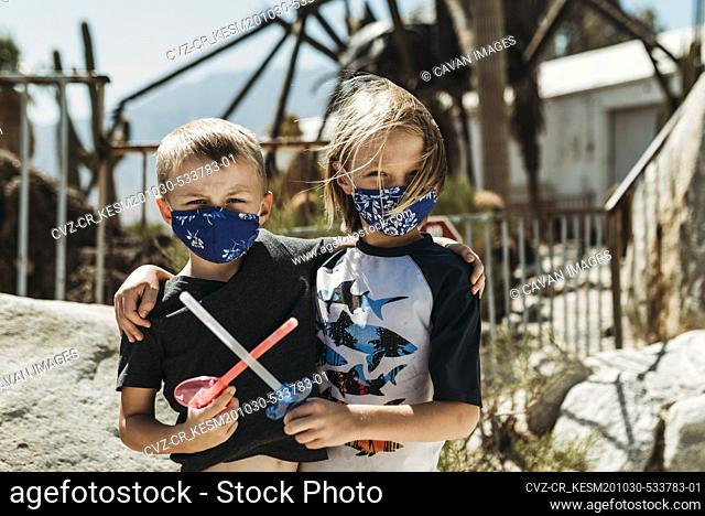 Close up portrait of young brothers with masks on outside on vacation