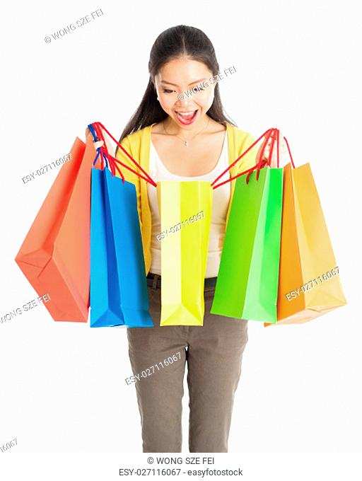 Happy young Asian female shopper, hands holding shopping bags and smiling, isolated standing on white background