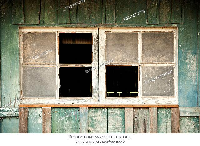 Broken windows of derelect horse barn, California