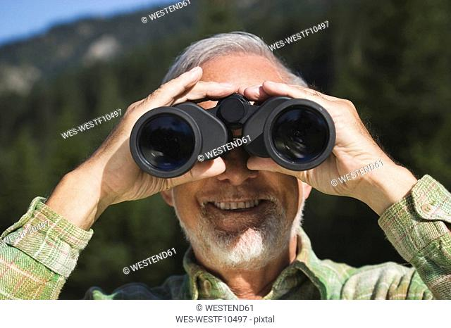 Austria, Karwendel, Senior man looking through binocular, portrait