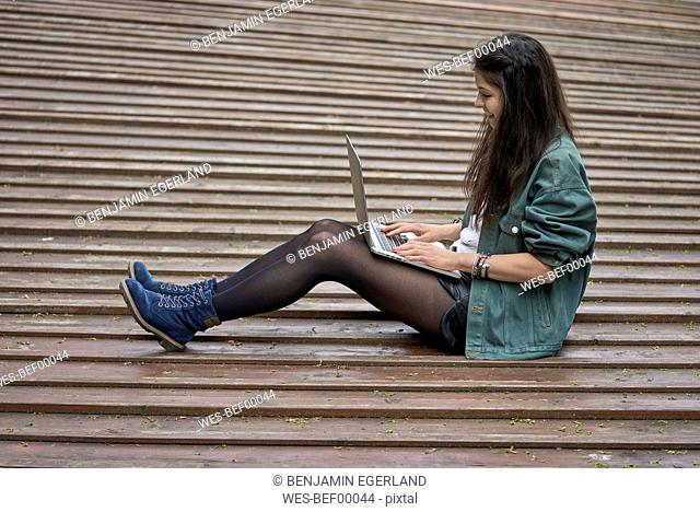 Young woman sitting on ground outdoors using laptop