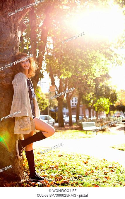 Woman leaning on tree in park