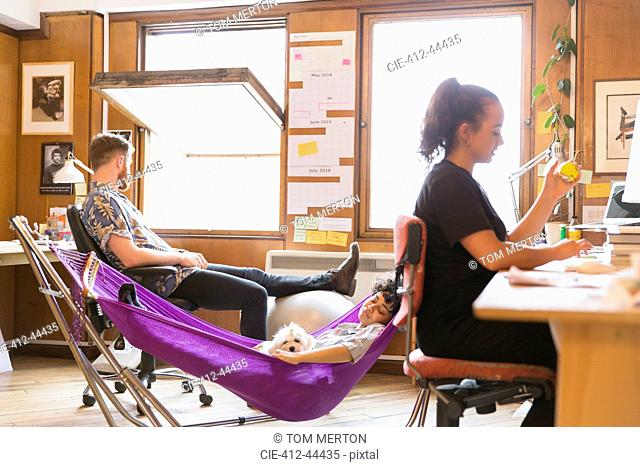 Creative female designer with dog napping in hammock in office