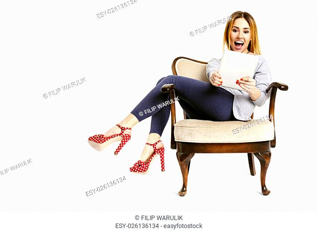 Studio shot of surprised woman sitting on armchair